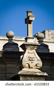 A stone cross erected on a base adorned with skulls found in the courtyard of St John's Co-Cathedral - built by the Knights of St John, Valletta, Malta.