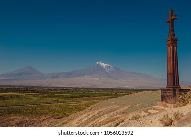 Stone cross khachkar on hill of Khor Virap Monastery. Mountain Ararat on background. Exploring Armenia. Tourism and travel concept. Religion landmark. Tourist attraction. Copy space for text. Blue sky