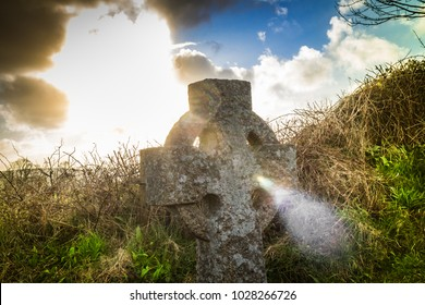 Stone cross with the light shining though it's centre. Grave yard with a godly light passing through tombstone.