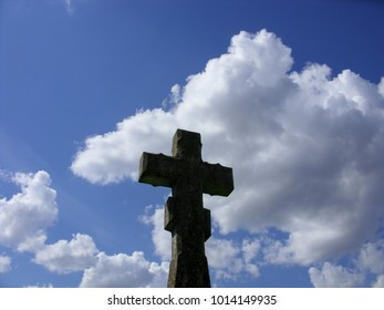 Stone cross at an old graveyard on summer sky background