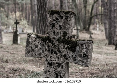 stone cross on a abandoned forest cemetery - poland
