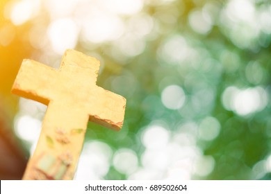 Stone Cross on nature green bokeh background.The Cross symbol of christian and Jesus Christ.