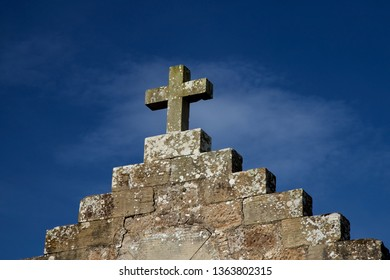 Stone cross on old building against a blue sky