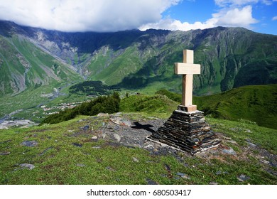 Stone cross on top of Kazbegi mountain landscape, Stepantsminda, in Gergeti village in Georgia on sunny day with blue sky. Inspirational faith and hope concept for Christianity. Travel and pilgrimage.