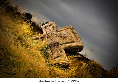 A stone cross in withered grass