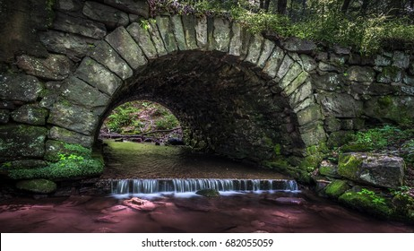 A stone culvert with stream passing under a road through Stokes State Forest, New Jersey