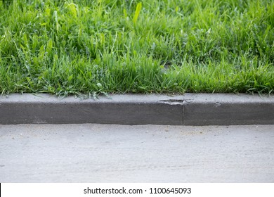stone curb near the road. background, grass