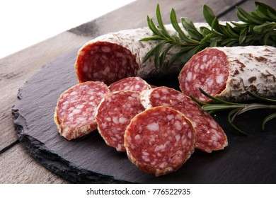 Stone cutting board with sliced salami on it