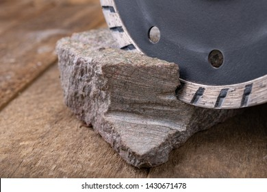 Stone cutting with a diamond disc mounted in a grinder. Work in a stone workshop. Dark background.