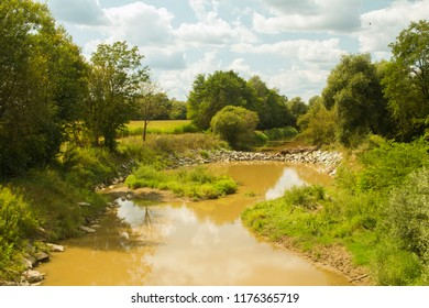 Stone dam and orange water of the Raab, Raba river. River landscape. Lower Austria. Burgenland. Central Europe.