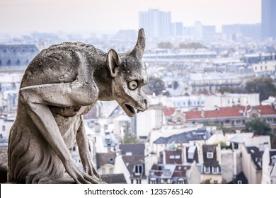 Stone demons gargoyle and chimera/ Paris city on background. View from Notre Dame de Paris, France