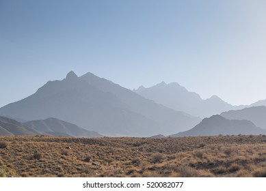 stone desert with dry plant and layers of mountain under clear blue sky, majestic landscape in Iran