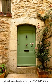 Stone doorway with climbing roses in medieval village of Valbonne, Provence, France