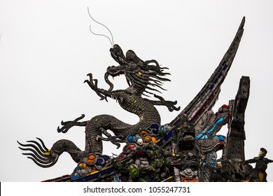 A stone dragon on the roof of the Mengjia Longshan Temple in Taipei, Taiwan is tinged black from exposure to the elements with bright glass decorations embedded at certain points.