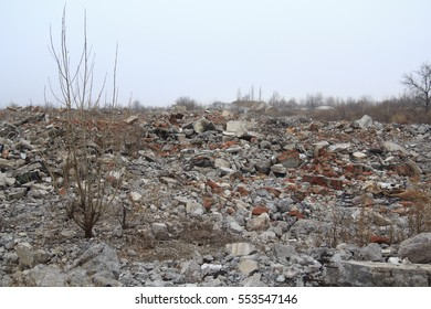 Stone dump on the site of destroyed building with a field of debris