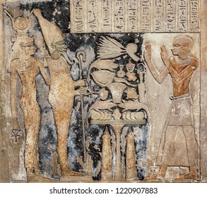 stone with elements of egyptian ancient history. pharaon, queen and priest with victim