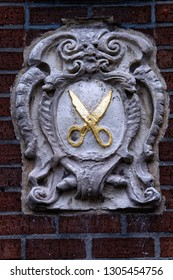 A stone emblem mounted on a brick wall consisting of scissors painted with gold paint surrounded by ornaments, decorating a historic house in the central part of Ghent, Belgium.