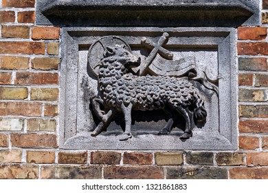 Stone emblem mounted on a brick wall consisting of a sheep, christian cross and a flag, decorating a historic house in the central part of Bruges, Belgium.