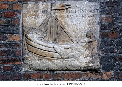 Stone emblem mounted on a brick wall consisting of a small merchant sail boat, decorating a historic house in the central part of Bruges, Belgium. Inscription  - not readable.