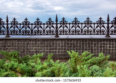 stone fence made of square tiles and with iron forged peaks with a pattern in a park with green bushes in the background a river and a cloudy sky.