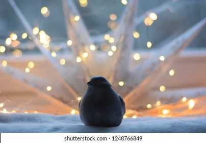 Stone figurine of a small bird in front of New Year's and Christmas lighting near the window. Metaphorical display of boastfulness, disdain, egoism, proud.