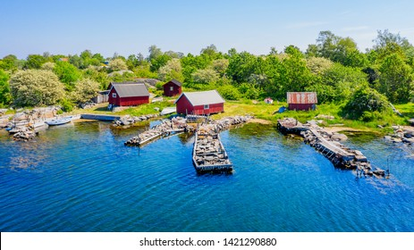 Stone filled jetties and fishing sheds seen from the sea. Location Hasslo island in Blekinge archipelago, Sweden.