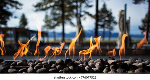 Stone Fire Pit with Flames and Trees in Background Outdoors