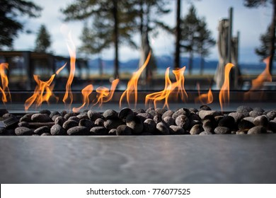 Stone Fireplace Fire Pit with Flames and Trees in Background Outdoors