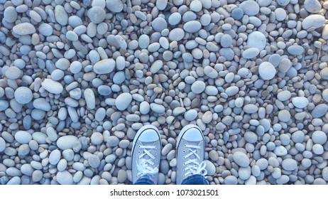 Stone floor on beach and shoes overhead view