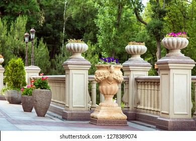 Stone flowerpots with flowers on pedestals between railings with baroque balustrades, retro lantern and green trees in the background.