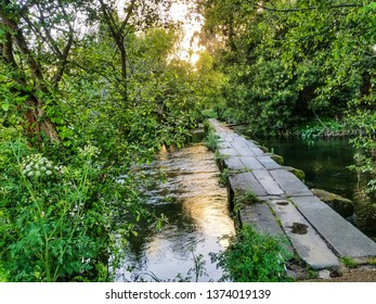 Stone footbridge over Umia river between riverbank forest in Acenhas de Baion, Vilanova de Arousa