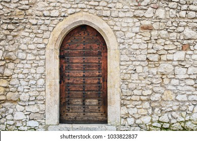 Stone fortress castle wall of a medieval castle, an old wooden closed arcade door with iron rivets.