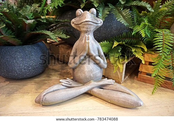 Stone frog sits in crossed legs gesture. Selective focus on the face of frog.