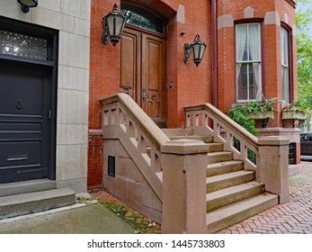 stone front step of elegant old urban brownstone type townhouse with double wooden door