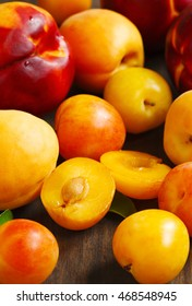 Stone fruits on wooden background. Yellow plums, apricots and nectarines.