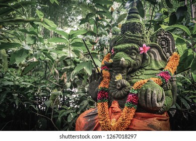 Stone Ganesha statue with the incense sticks and orange flowers decorated for religious festival and ceremonial offering, Bali.