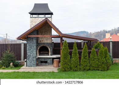 Stone garden oven for grill or barbeque is in a backyard. Backyard patio area with fireplace. BBQ area