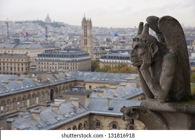 Stone gargoyle (Chimera) overlooking the city of Paris from the tower of the Notre Dame with the Sacr���©-Coeur in the background