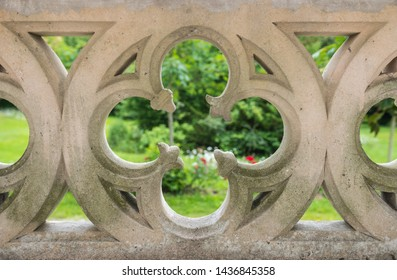 Stone gate shaped like a Four-leaf clover (Flers, Normandy, France). Beautiful pattern. Green landscape in the background. Close up of this magnificent piece of architecture.