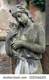 The stone Girl on Tomb from the snowy winter old Prague Cemetery, Czech Republic
