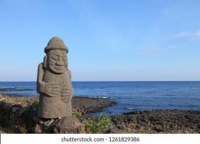 Stone Grandfather (Dolhareubang) and Jeju Island Coastal Landscape - Dolhareubang is a guardian guarding ancient villages of Jeju Island, Korea