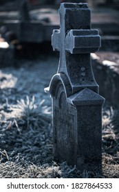Stone grave tomb cross monument in a morning autumn frost as All Souls Day, All Saints Day background