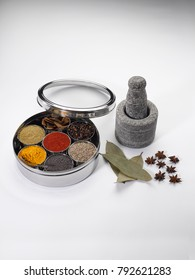 Stone grinder and pestle with stainless masala dabba on a white background