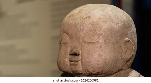 Stone head of smiling maitreya buddha