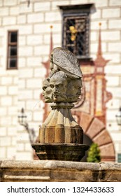 Stone heads spitting water on the fountain in front of Trebon castle