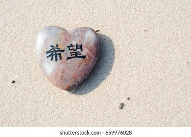 "Stone heart with Japanese characters meaning ""hope"" on the beach"
