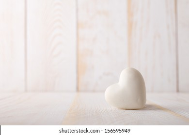 Stone heart on the white wooden background.