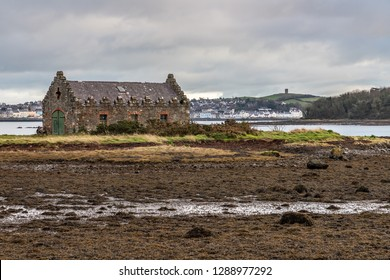 Stone house in Strangford lough with Portaferry village in background, Northern Ireland, UK
