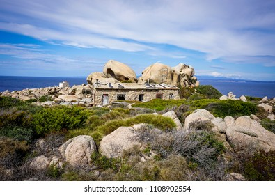 stone house surrounded by grass and rocks with the ocean view. Capo Testa, Sardinia, Italy
