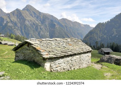 A stone hut in the Walser town of Follu, among high mountains, pine forests and green pastures, in summer, in Val d'Otro valley, Alps mountains, Italy